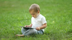stock-footage-baby-boy-working-with-the-tablet-pc-sitting-on-the-grass